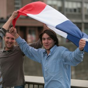 3 boys holding up the flag of France
