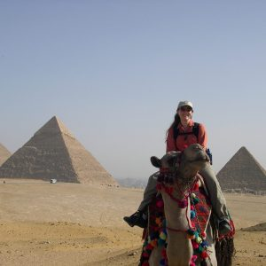 Woman riding a camel in front of Pyramids