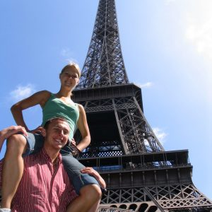 Girl on shoulders of boy in front of Eiffel tower