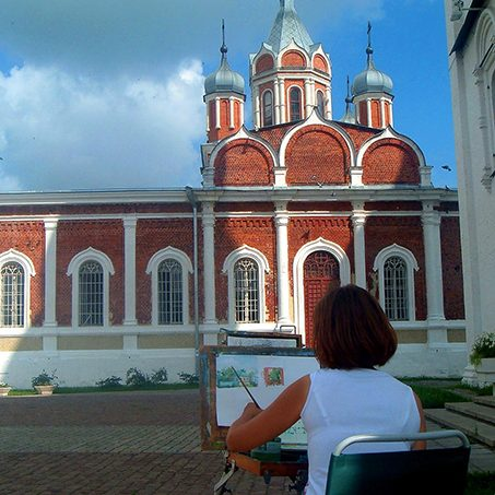 Woman sitting and painting a church